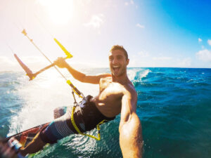 Find out the best Maui adventures you should book before your trip recommended by top Hawaii blog Hawaii Travel with Kids. Image of a man kiteboarding on Maui.