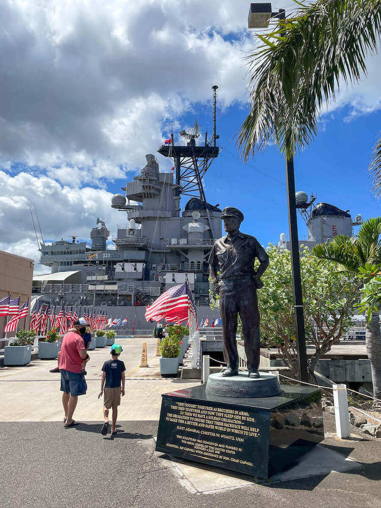 Find out whether or not it's worth visiting Pearl Harbor with kids. Image of a dad and two boys walking through the entrance to the USS Battleship Missouri at Pearl Harbor.