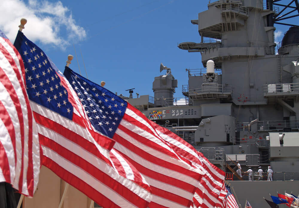 Image of American flags flying in front of the USS Battleship Missouri at Pearl Harbor on Oahu.