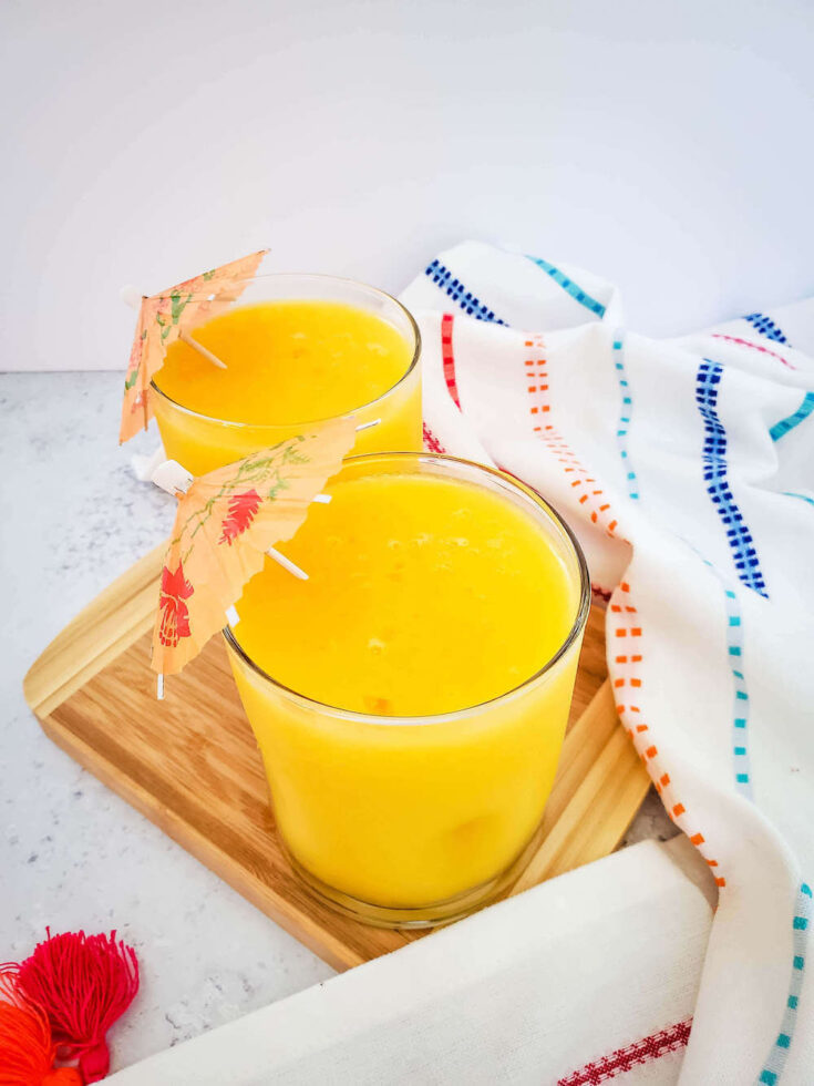 Find out how to make this frozen mango margarita recipe by top Hawaii blog Hawaii Travel with Kids. Image of a bright orange tropical cocktail in 2 glasses with little umbrellas.