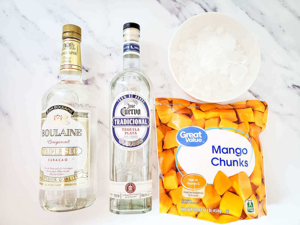 These are the ingredients you'll need to make frozen mango margaritas. Image of tequila, triple sec, a bag of frozen mango chunks, and a bowl of ice.