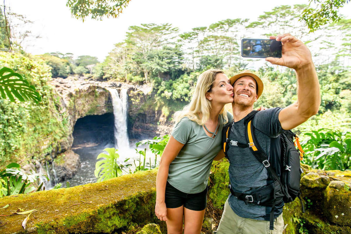 Check out more than 100 Hawaii captions for Instagram by top Hawaii blog Hawaii Travel with Kids! Image of a man and woman taking a selfie at Rainbow Falls on the Big Island of Hawaii