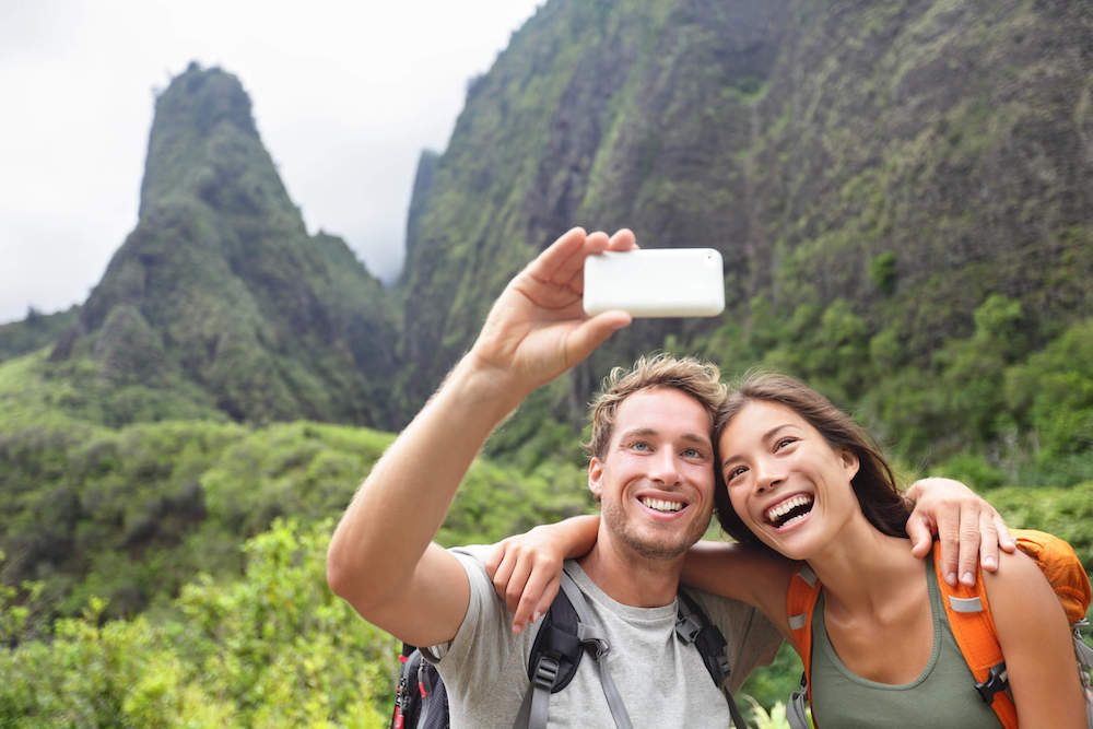 There are plenty of Maui Instagram captions you can use for your Maui selfies! Image of a man and woman taking a selfie at I'ao Needle on Maui.