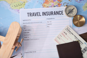Find out whether or not you really need Hawaii travel insurance by top Hawaii blog Hawaii Travel with Kids. Image of some travel insurance paperwork on top of a map.
