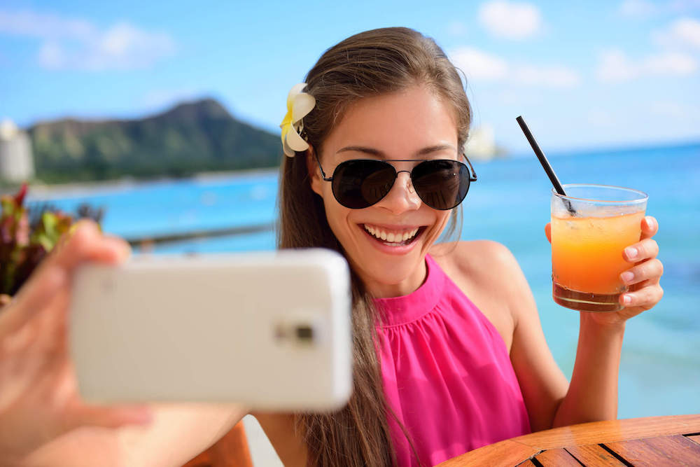 These tropical drink Instagram captions are perfect for your trip to Hawaii. Image of a woman holding a mai mai while taking a selfie in Waikiki.