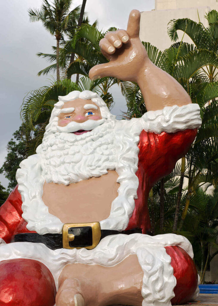 Honolulu City Lights is one of the most popular Waikiki Christmas events. Image of a giant Santa statue waving a shaka sign.