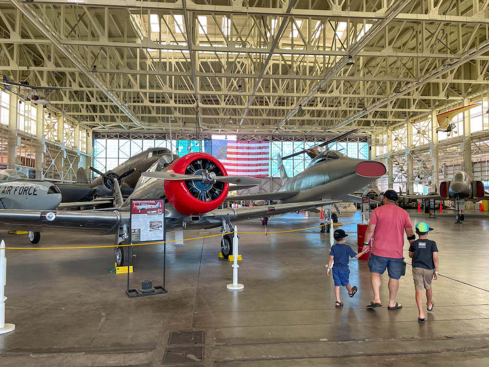Interior of Hangar 79 of the Pearl Harbor Aviation Museum. Image of a dad and two little boys walking around the airplane museum.