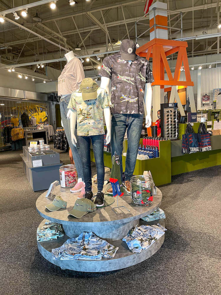 The Pearl Harbor Aviation Museum gift shop is full of all kinds of Pearl Harbor souvenirs. Image of a display of Aloha shirts, hats, and other airplane-themed items.