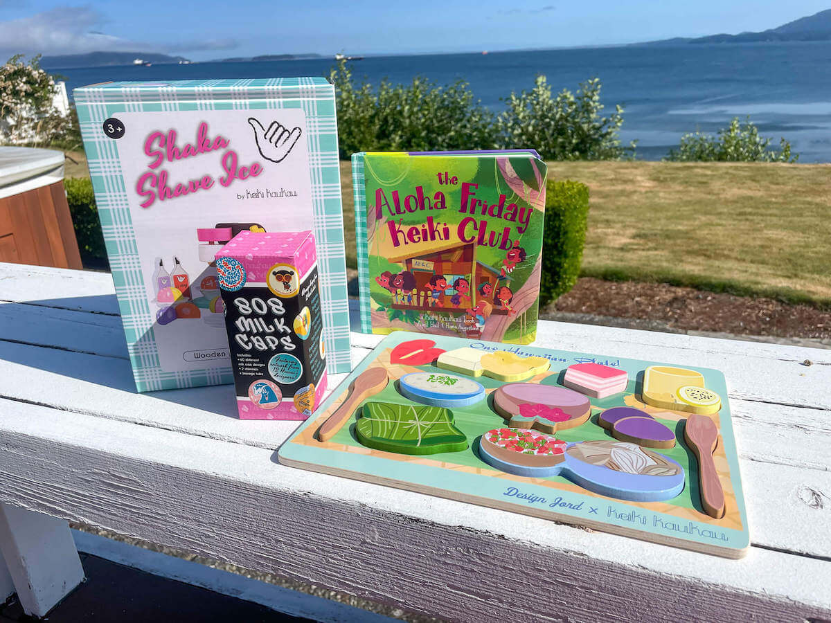 Looking for cute Hawaiian gifts for kids? Check out Keiki Kaukau, the best place for Hawaiian toys recommended by top Hawaii blog Hawaii Travel with Kids. Image of a wooden shave ice play set, pogs, wooden puzzle, and Hawaiian book.