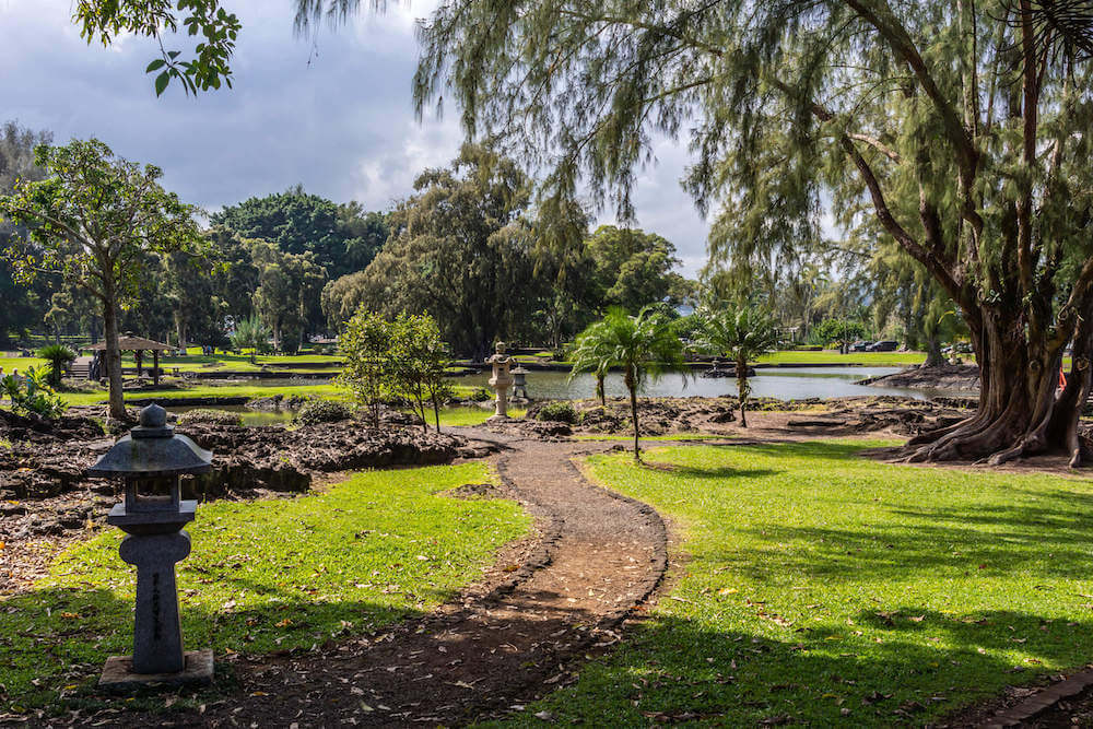 One of the prettiest Hilo botanical gardens is Liliuokalani Gardens. Image of a pathway leading to water in Hawaii.