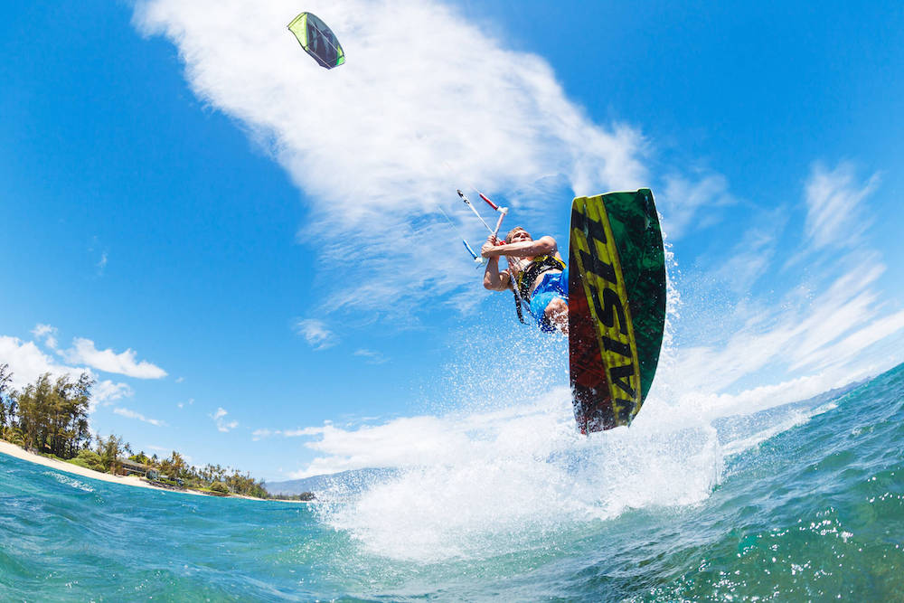 Learn how to kiteboard on Maui with this Maui kiteboarding group lesson. Image of a man kiteboarding on Maui.