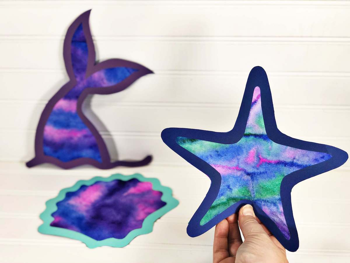 Find out how to make ocean animal coffee filter suncatchers by top Hawaii blog Hawaii Travel with Kids. Image of a starfish, memaid tail, and seashell suncatcher.