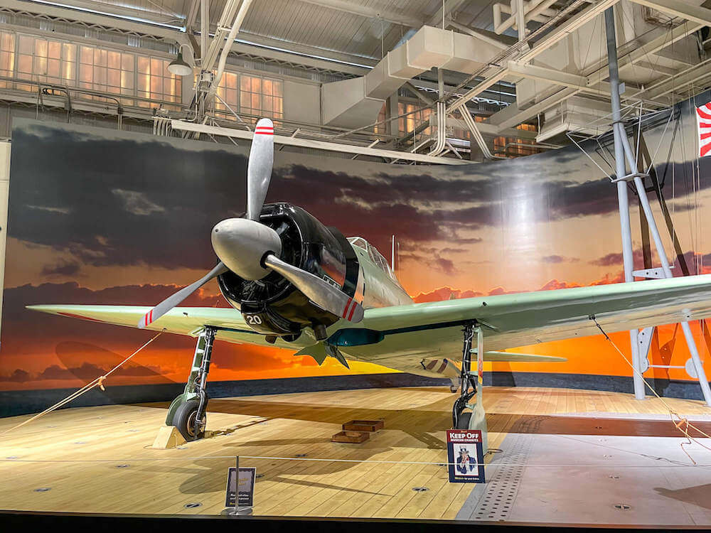 Image of a Mitsubishi A6M2 Model 21 Type 0 airplane on display at the Pearl Harbor Aviation Museum in Hawaii.