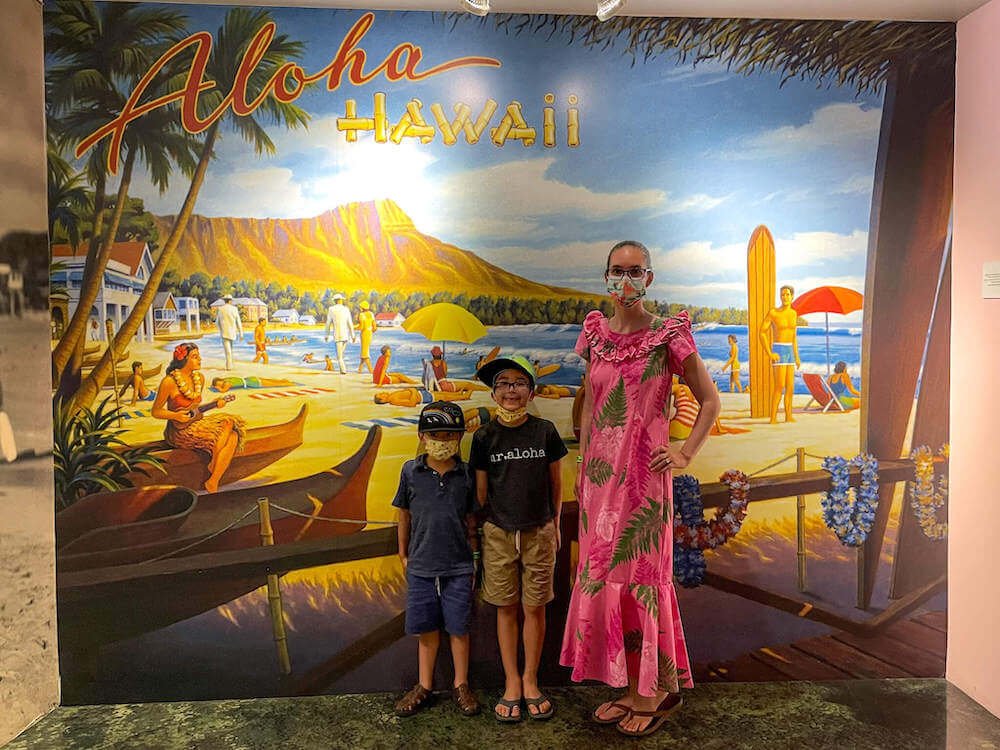 Wondering what to wear to Pearl Harbor? You can keep it casual with a t-shirt and shorts, or dress up a bit with Aloha wear. Image of a mom wearing a pink mu'u mu'u and two boys wearing t-shirts and shorts at the Pearl Harbor Aviation Museum.
