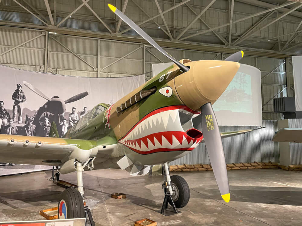 Planning to visit Pearl Harbor with kids? Read this Pearl Harbor Aviation Museum review by top Hawaii blog Hawaii Travel with Kids. Image of a WWII airplane painted with a face with sharp teeth.