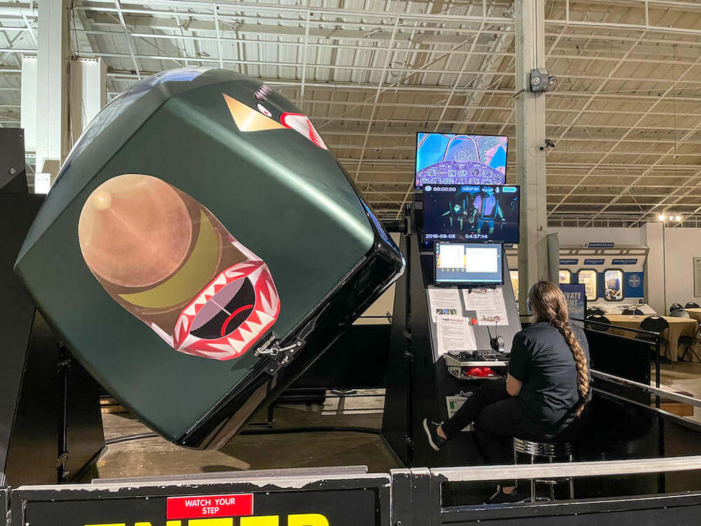 There are really cool Fighter Ace 360 flight simulators at the Pearl Harbor Aviation Museum. Image of a woman running the flight simulator.