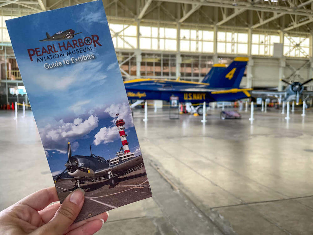 Image of a woman holding a Pearl Harbor Aviation Museum brochure with a Blue Angel airplane in the background.