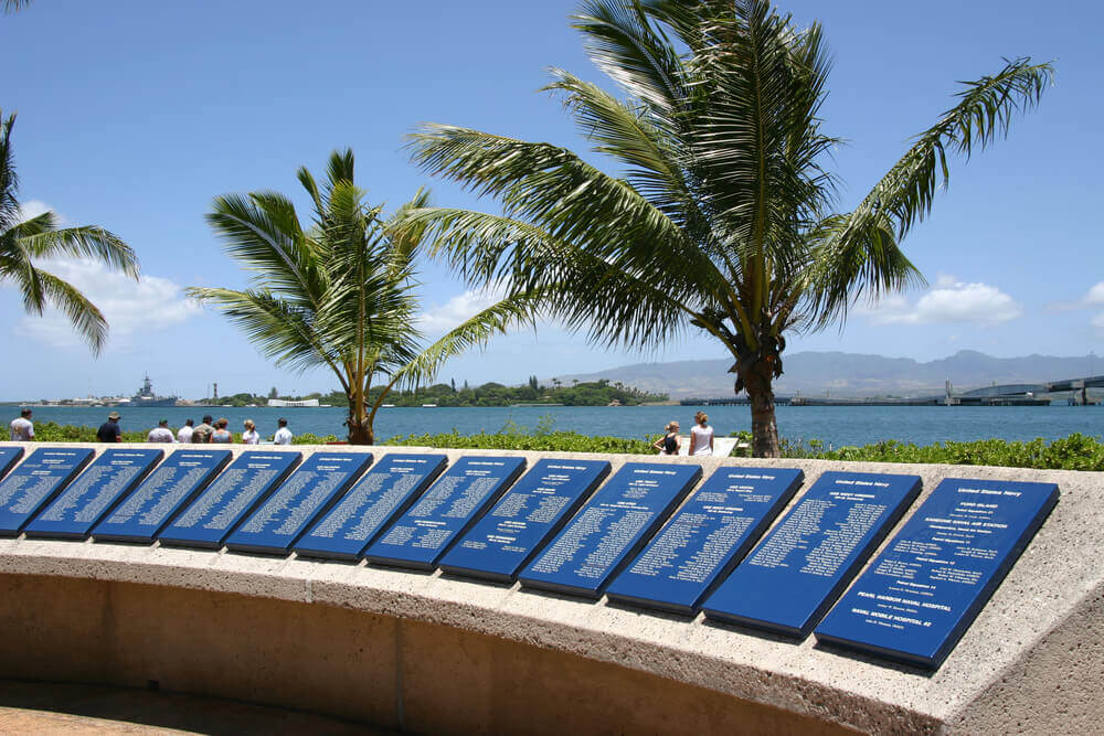 Image of a row of plaques with palm trees in the background at the Pearl Harbor memorial.