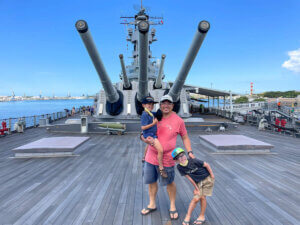 Find out whether or not it's worth visiting Pearl Harbor with kids by top Hawaii blog Hawaii Travel with Kids. Image of a dad and two boys posing on the deck of the USS Battleship Missouri