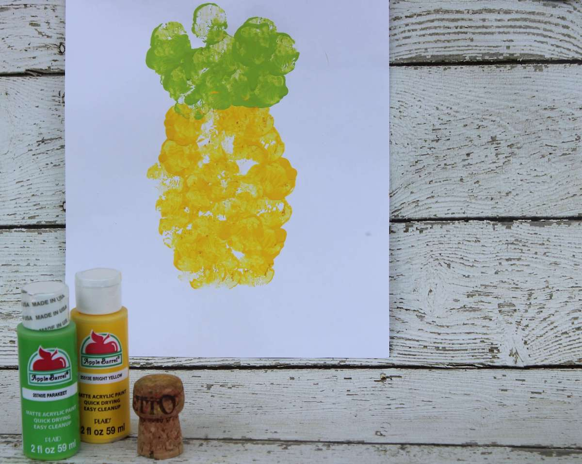 Learn how to make this adorable pineapple craft for toddlers by top Hawaii blog Hawaii Travel with Kids. Image of a pineapple painting done with cork stamping.