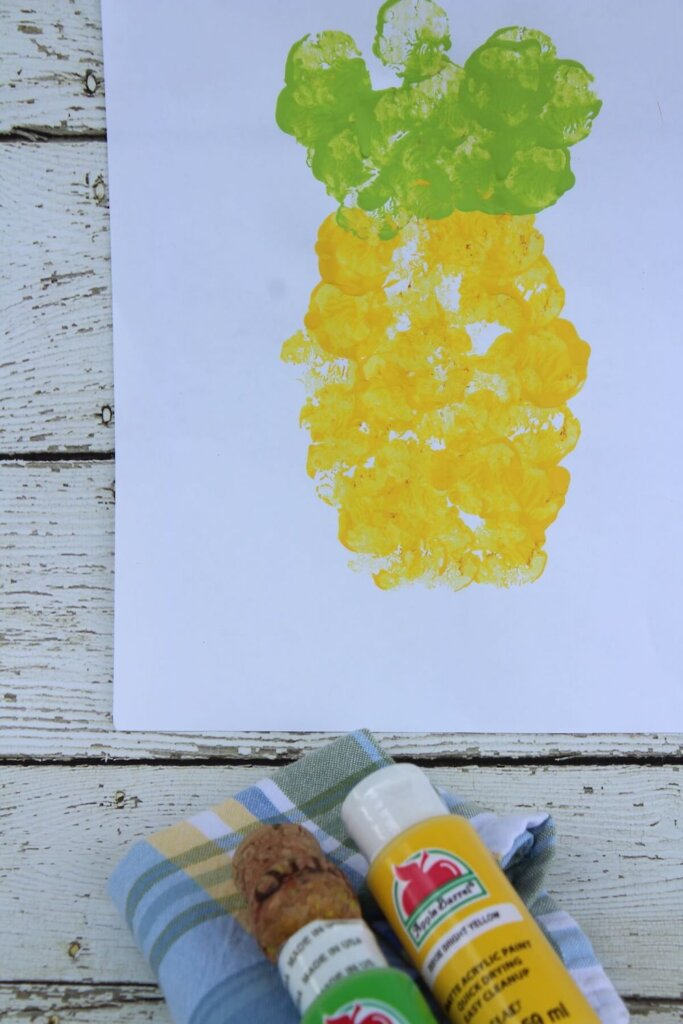 And now you know how to complete this simple pineapple craft for toddlers. Image of a piece of white paper with yellow and green stamps to form a pineapple.