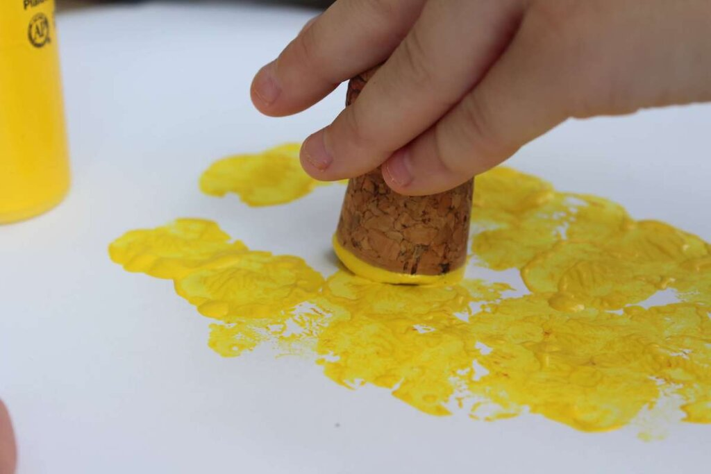 Learn how to make this pineapple craft for toddlers by top Hawaii blog Hawaii Travel with Kids. Image of a kid using a cork to stamp yellow paint on paper.