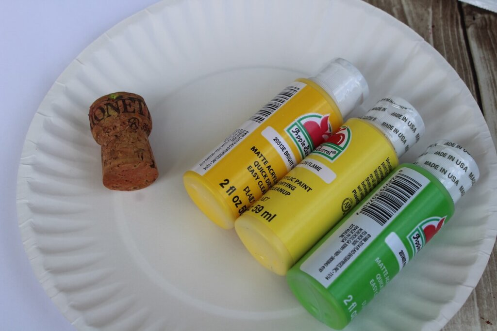 You really only need a few supplies for this simple pineapple craft for kids. Image of a paper plate with little bottles of yellow and green paint, and a wine cork.