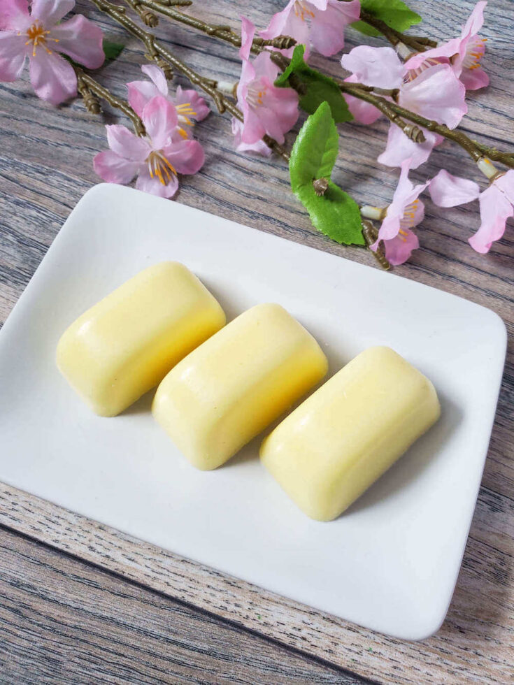 Find out how to make these pineapple sugar scrub bars from top Hawaii blog Hawaii Travel with Kids. Image of three yellow sugar scrub bars on a white plate with stems of pink flowers.