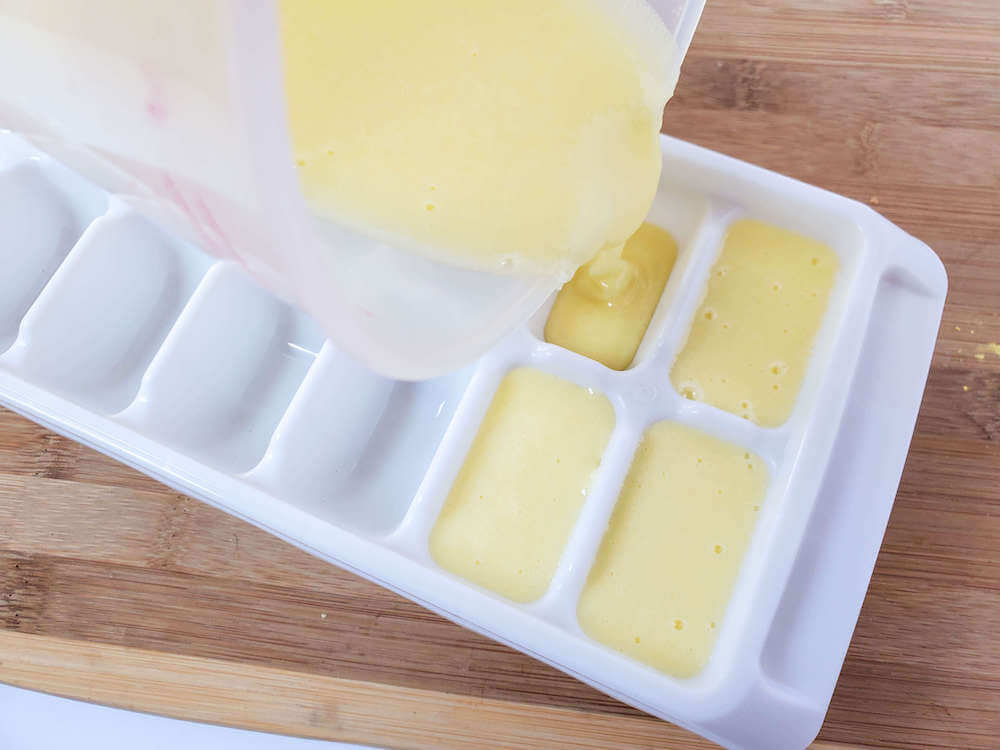 Pour your pineapple sugar scrub mixture into an ice cube tray. Image of someone pouring yellow liquid into a white ice cube tray.