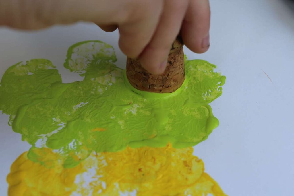 Learn how to make this easy pineapple craft for toddlers using paint and a wine cork. Image of a kid using a cork to stamp green paint on paper.