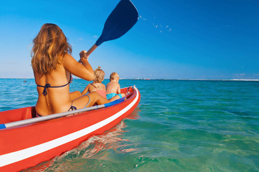 Find out the top tips for kayaking with kids in Hawaii by top Hawaii blog Hawaii Travel with Kids. Image of a mom and two kids in a red kayak on the ocean.