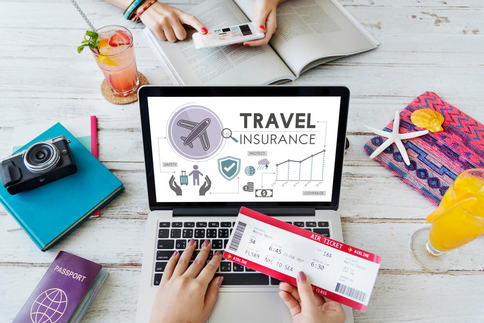 Find the right Hawaii travel insurance plan for your family. Image of a woman holding an airplane ticket in front of a laptop that says travel insurance on the screen.