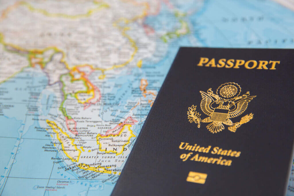 Wondering if you need a passport to visit Hawaii? As long as you are visiting from the US, you don't! Image of a US passport on top of a world map.
