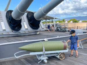 Find out whether or not to bring kids to the USS Battleship Missouri at Pearl Harbor in this post by top Hawaii blog Hawaii Travel with Kids. Image of a boy standing on main deck of the USS Battleship Missouri.