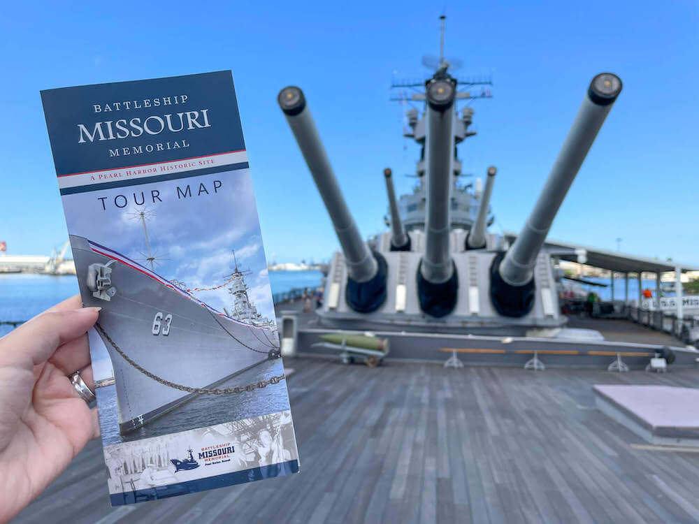 Remember to grab a tour map of the Battleship Missouri Memorial at Pearl Harbor. Image of a woman holding a tour map brochure with the USS Battleship Missouri in the background.