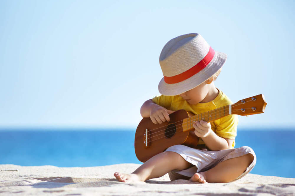 Find out where to find vacation babysitters in Hawaii recommended by top Hawaii blog Hawaii Travel with Kids. Imag eof a boy playing an ukulele on the beach.
