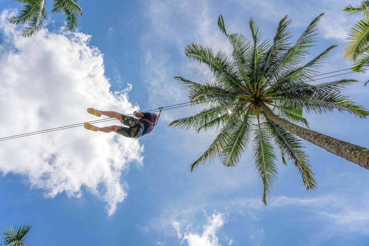 Find out the best places to go ziplining in Hawaii recommended by top Hawaii blog Hawaii Travel with Kids. Image of someone ziplining between palm trees with the sky in the background.