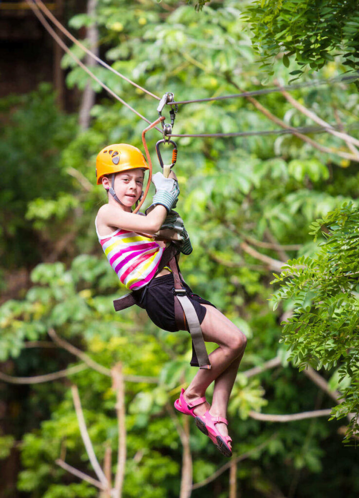 Find out my top tips for ziplining in Hawaii for beginners. Image of a girl ziplining in the jungle.