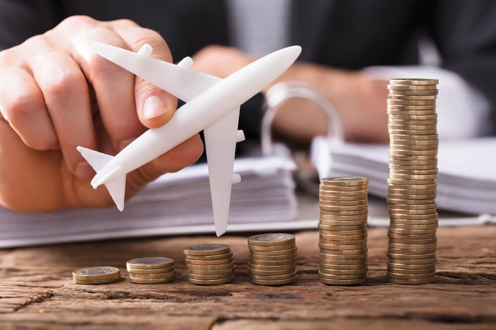 Find the right Hawaii travel insurance plan that fits your Hawaii budget. Image of someone holding a toy airplane next to stacks of coins.