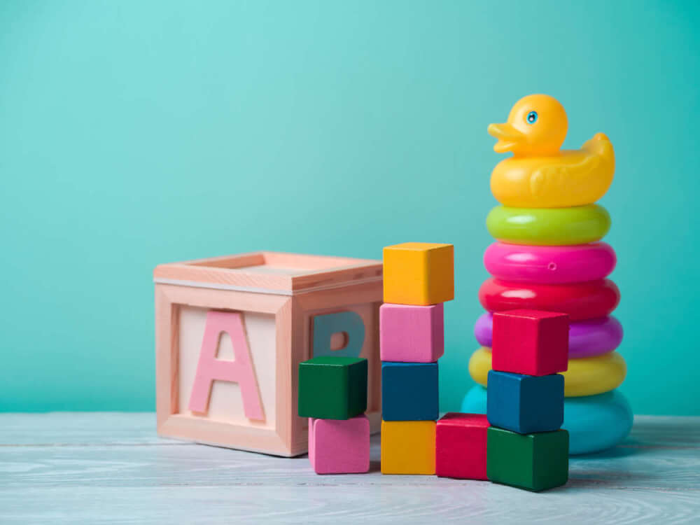 Find out the best Oahu baby stores recommended by top Hawaii blog Hawaii Travel with Kids. Image of baby toys with a teal background.
