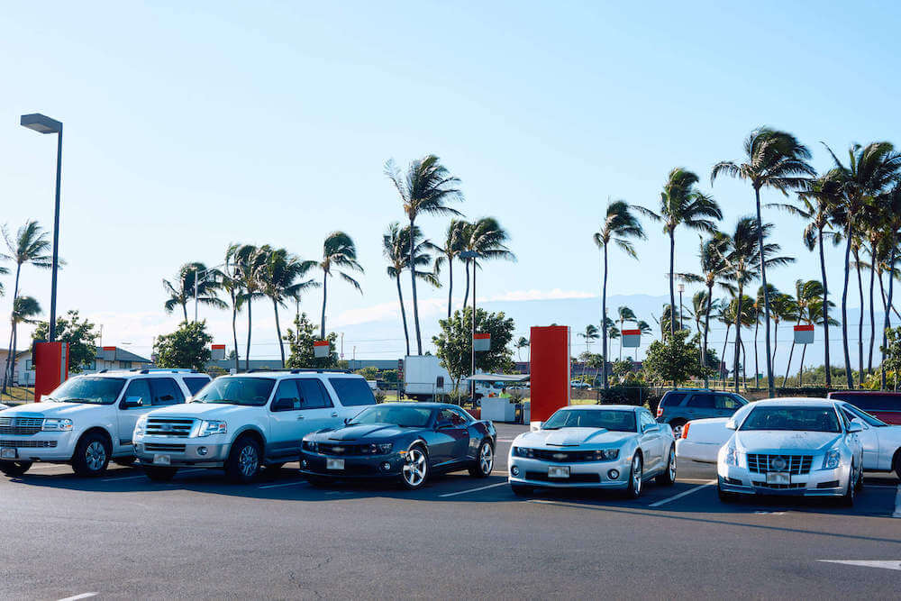 Find out where to get cheap Maui car rentals recommended by top Hawaii blog Hawaii Travel with Kids. Image of a bunch of renal cars in Hawaii.