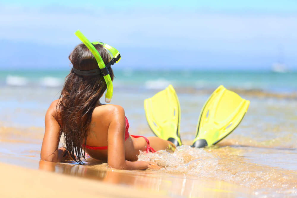Find out how to visit Maui on a budget by top Hawaii blog Hawaii Travel with Kids. Image of a woman wearing snorkeling gear laying at the beach in Maui.