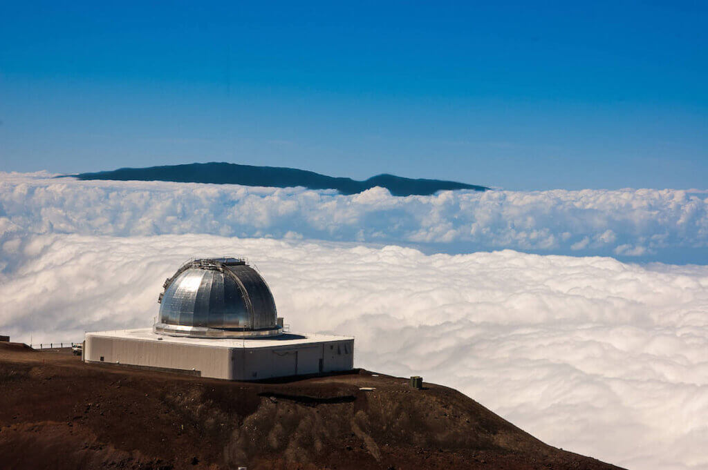 Image of the Mauna Kea Observatory surrounded by a field of snow.