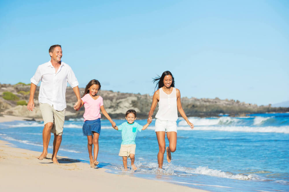 Find out the things I wish I knew before going to Hawaii with kids. Image of a family walking on the beach in Hawaii
