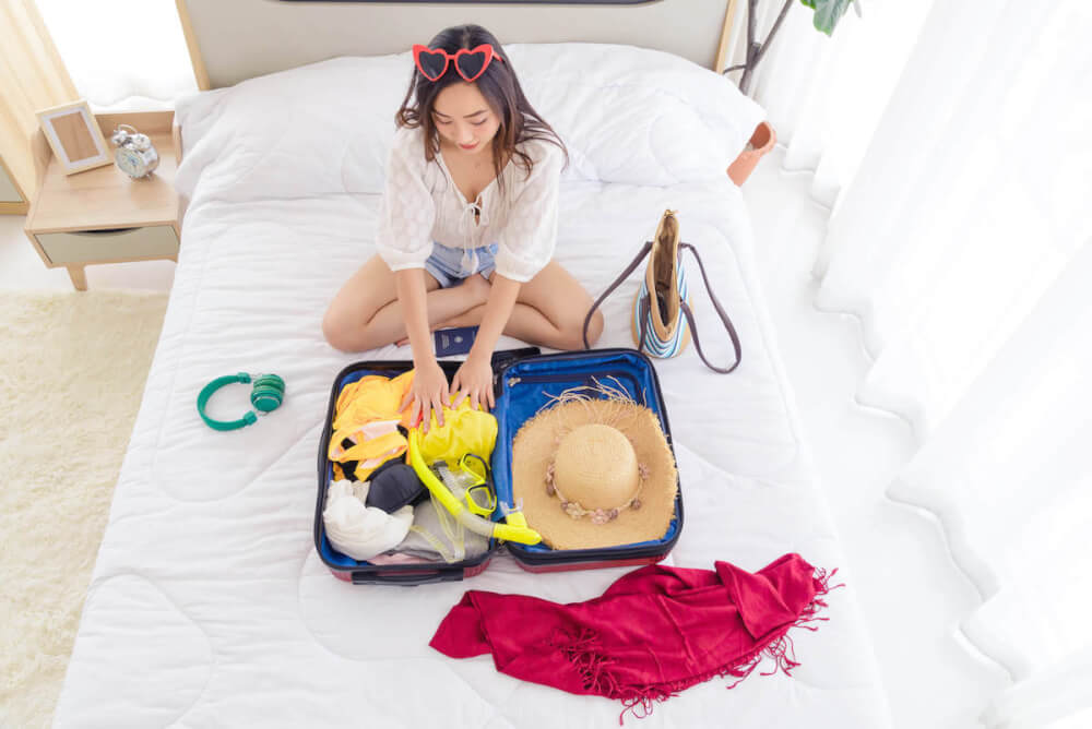 Find out the best things to bring to Hawaii recommended by top Hawaii blog Hawaii Travel with Kids. Image of a woman packing a suitcase on a white bed.