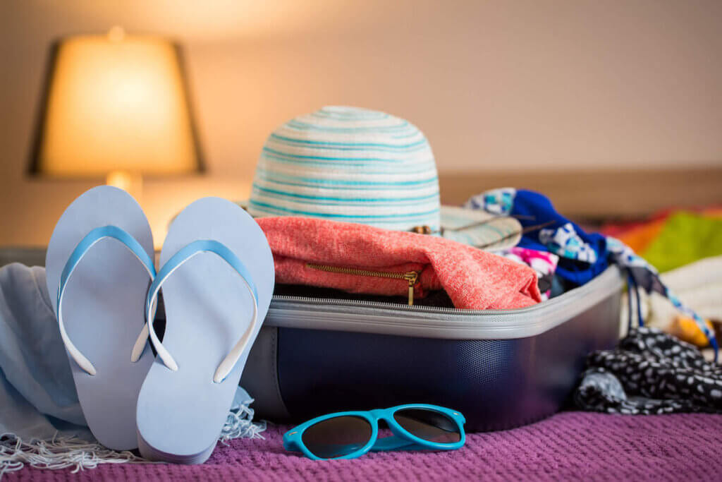 Find out the best things to pack for Hawaii recommended by top Hawaii blog Hawaii Travel with Kids. Image of an open suitcase with flip flops, sunglasses, a sun hat, and beach clothing.