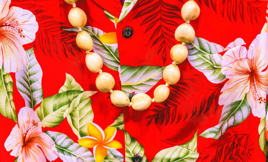 Find out the best Hawaii souvenirs worth buying according to top Hawaii blog Hawaii Travel with Kids. Image of a red Aloha shirt with a white kukui nut lei.