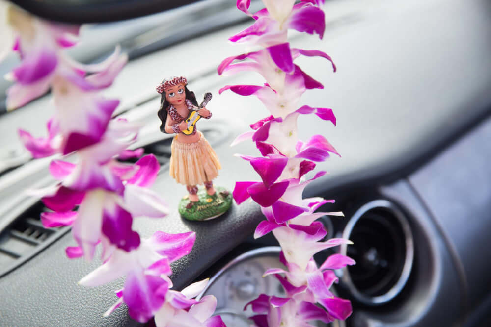 Find out where to buy Hawaiian souvenirs online by top Hawaii blog Hawaii Travel with Kids. Image of a purple lei and dashboard hula doll in a car.