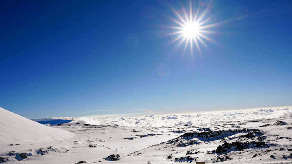 Find out how to go skiing in Hawaii by top Hawaii blog Hawaii Travel with Kids. Image of snow at Mauna Kea on the Big Island of Hawaii.