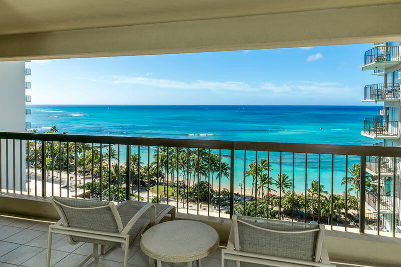 One of the best places to stay in Waikiki is the Aston Waikiki Beach Tower. Image of a lanai with a sweeping view of Waikiki beach and the Pacific Ocean.